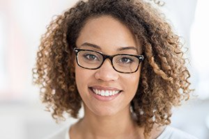 Lady with curly hair & glasses grinning after porcelain veneers