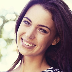 Brunette lady tilting her head smiling after periodontal therapy
