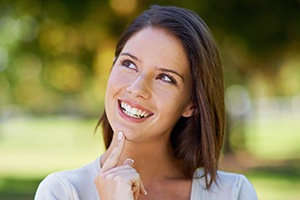Woman looking up and smiling after gum disease treatment