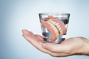 Hand holding glass of water with denture inside