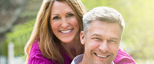 Man and woman sharing healthy smiles after restorative dentistry