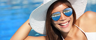 Woman in sun hat sharing flawless smile after cosmetic dentistry