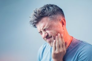 person suffering from tooth pain